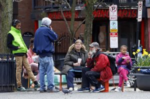 A group of people, not practicing social distancing, gather in Market Square in downtown Pittsburgh at lunchtime, Wednesday, April 1, 2020. (AP Photo/Gene J. Puskar)